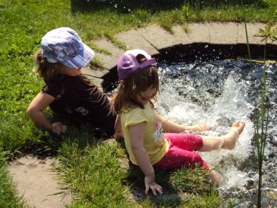 little girl splashing feet in backyard pond