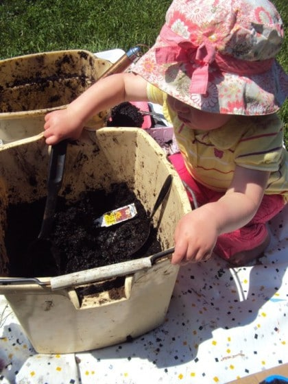 Toddler digging in bucket of mud