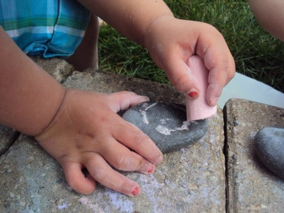 preschooler drawing with chalk on a stone