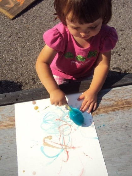 Toddler painting outdoors with ice