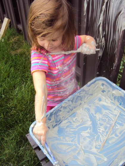 toddler painting arm with shaving cream