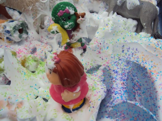 toys in the shaving cream and glitter sensory bin
