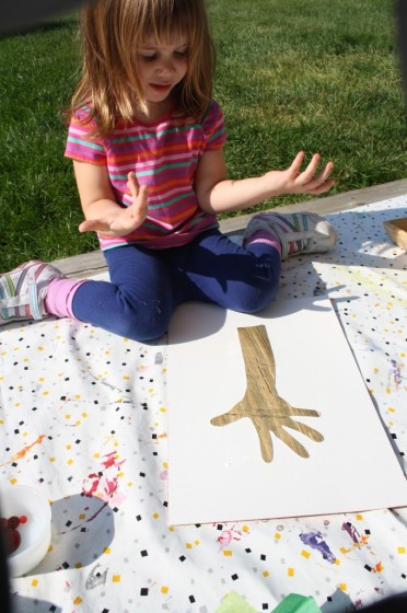 toddler tracing hand on brown paper