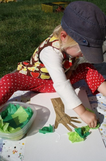 toddler gluing green tissue paper on apple tree craft