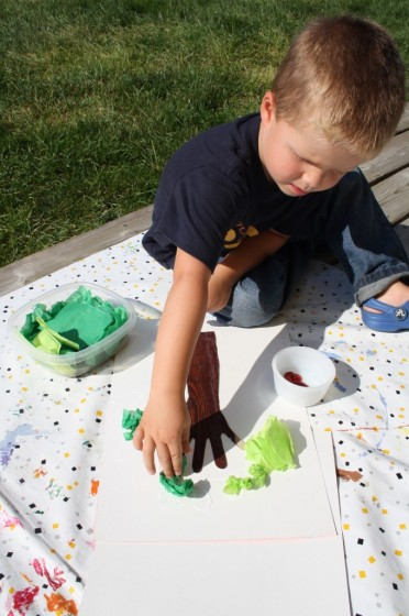toddler gluing crumpled tissue paper on paper apple treet
