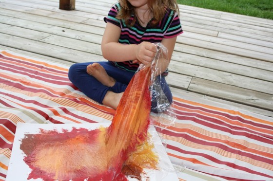 toddler pulling plastic wrap off wet paint
