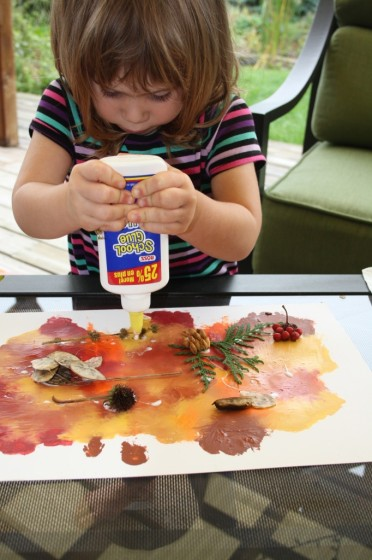 toddler gluing fall leaves to smoosh painted backdrop for collage