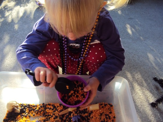 toddler playing with lentils in halloween sensory bin