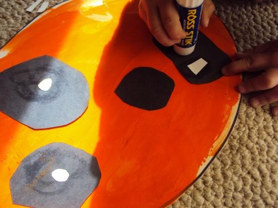 Toddler gluing paper jack o lantern