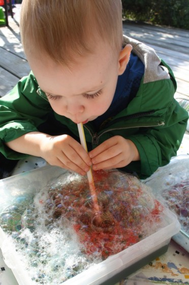 toddler blowing coloured bubbles to make bubble painting