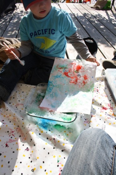 preschool boy pressing paper into bubble painting