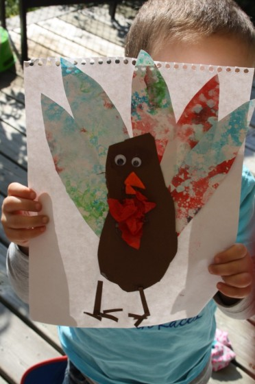 preschooler holding up finished bubble painting footprint turkey craft