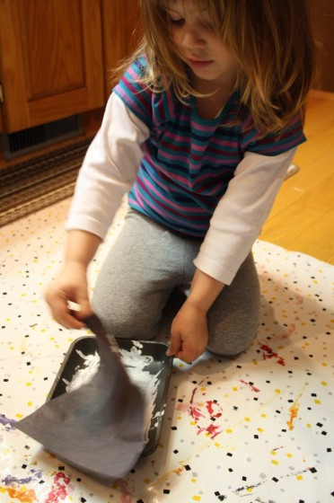 preschooler pressing black construction paper into white paint