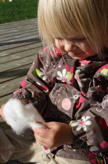 toddler pulling apart cotton ball