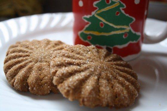 2 baked ginger cookies on plate beside Christmas mug