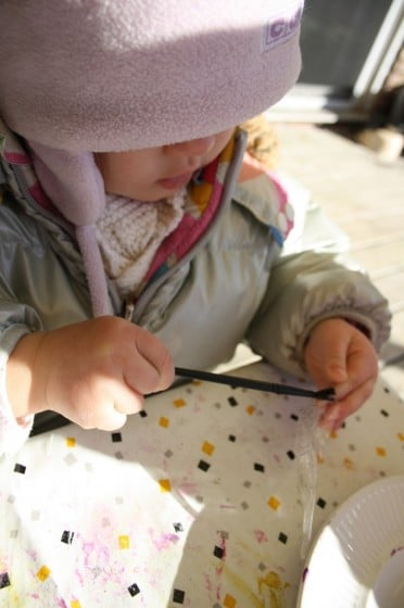 toddler painting glue on plastic icicle