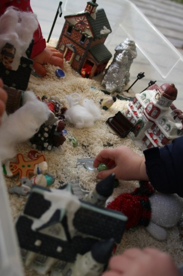 preschoolers playing in Christmas sensory bin of rice and village houses and people