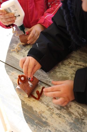preschoolers gluing eyes on their ornaments