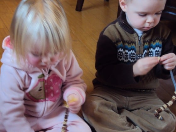 2 toddlers putting cheerios on pipe cleaners