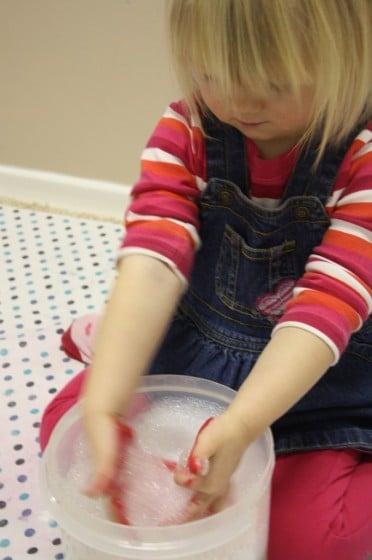 toddler washing paint off hands