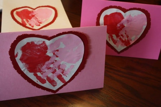 3 valentines cards with red and pink hand prints shaped like hearts