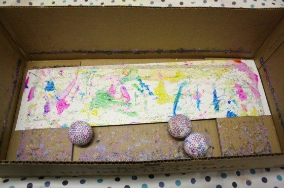 golf balls, paint and paper in cardboard box