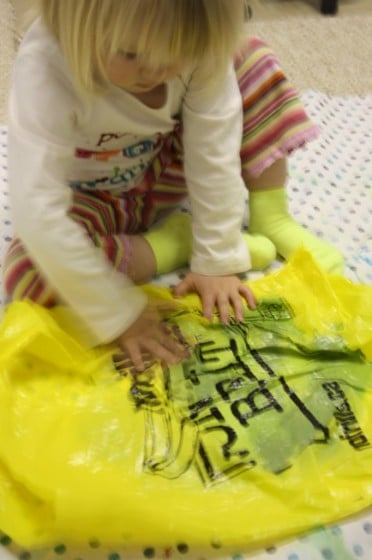 toddler smooching paint on paper in yellow plastic bag