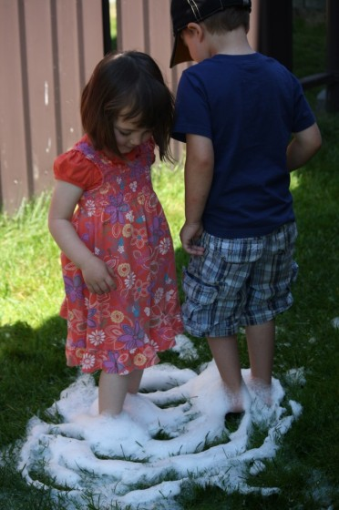 toddler and preschooler standing in soapy water on grass