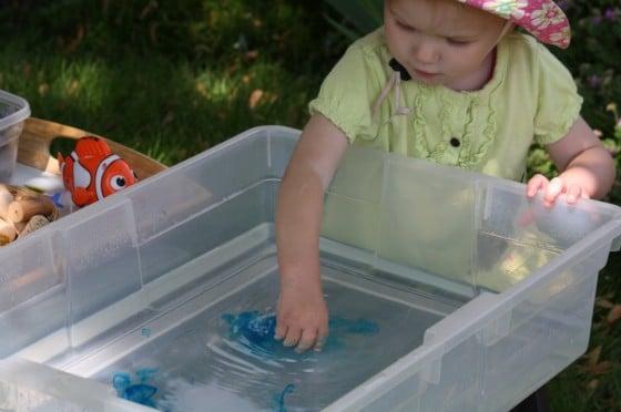 toddler playing in ocean sensory bin