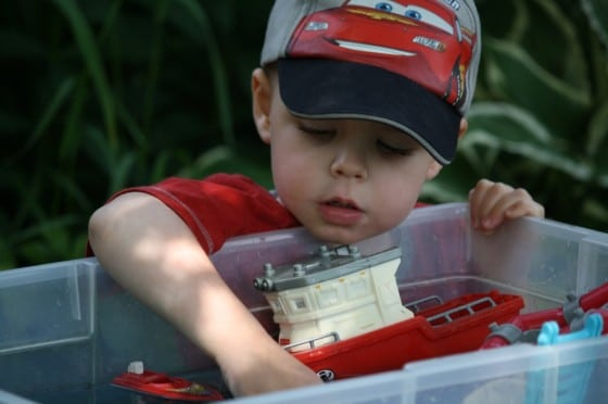 toddler boy playing with boats in bin of water