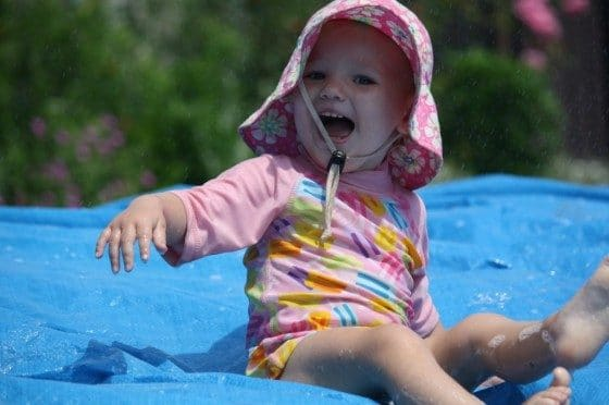 toddler on backyard water slide