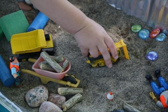 child pushing bulldozer in sand