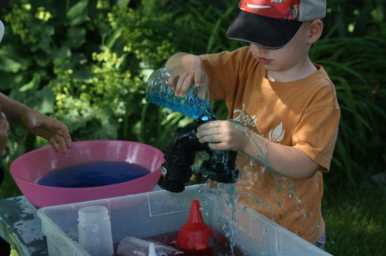 toddler pouring water through funnel during a science activity