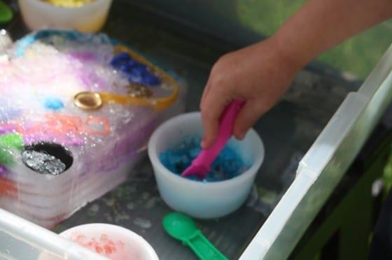 preschooler scooping blue salt on ice block with toys frozen inside