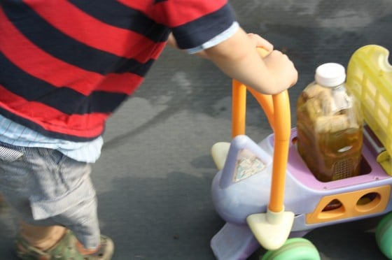 2 year old boy pushing bottle baby in ride on toy
