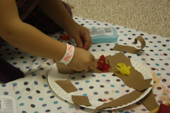 preschooler gluing crumpled tissue paper to paper plate fall wreath