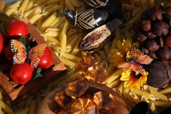 artificial apples, monarchs, amber gems and pinecones in fall bin