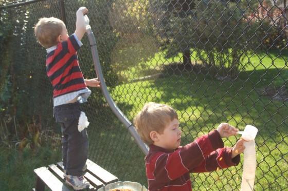 preschool boys pouring corn kernels into hoses