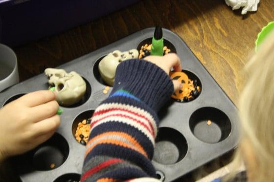 transferring and sorting sensory bin items in a mini muffin tin