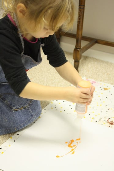child squeezing paint for pumpkin art