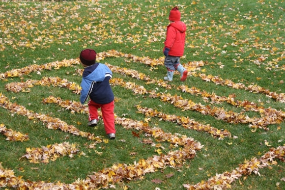 toddler and preschooler running through leaf maze