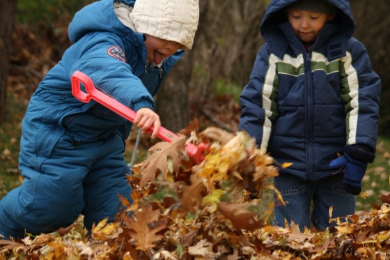 boy in blue snow suit adding leaves to pile at bottom of slide