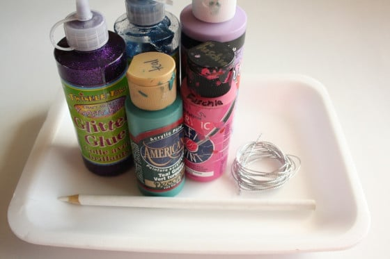 paint, styrofoam tray, glitter glue, white pencil crayon, string
