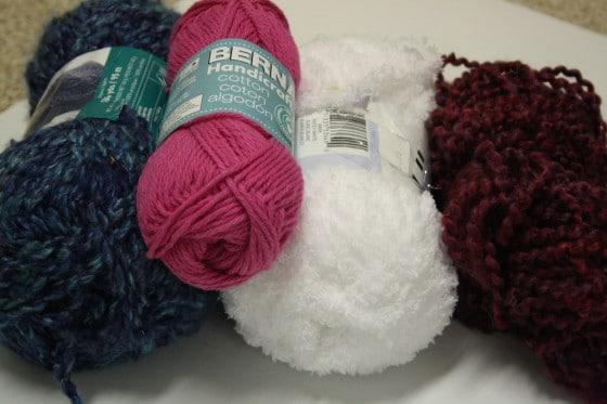 balls of yarn blue, pink, white, maroon