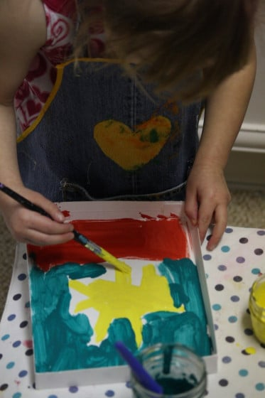 preschooler painting in box lid