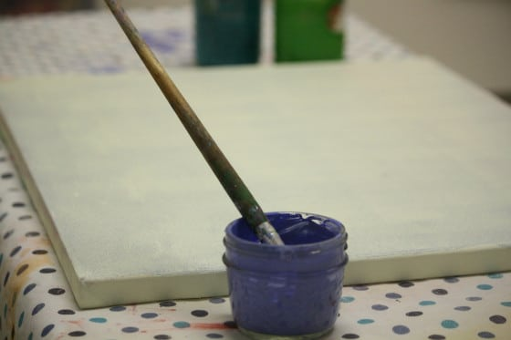 blue paint and paintbrush in front of primed canvas