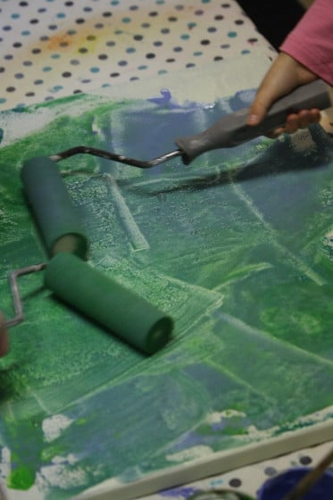 toddlers rolling green paint on canvas