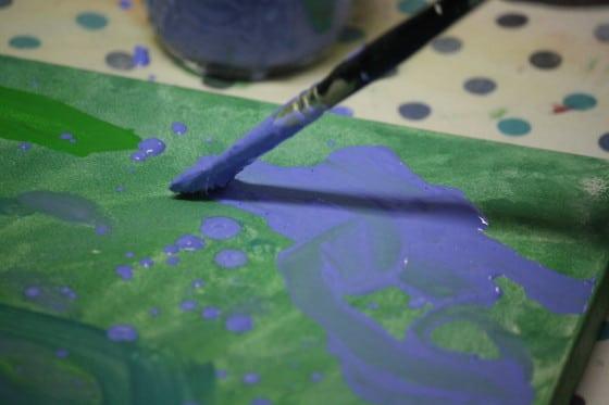 close up child's paintbrush with blue tempura paint