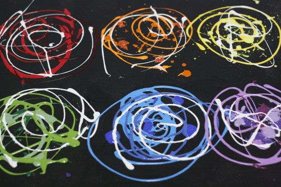 paint colours swirled on black canvas