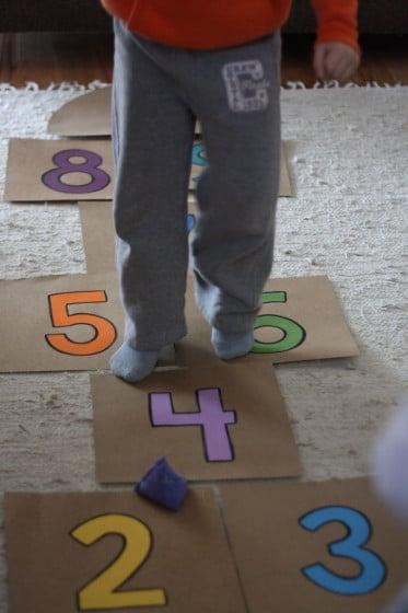 boy jumping on cardboard hopscotch